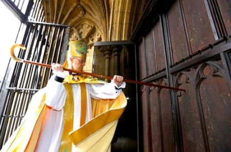 Archbishop Justin Welby knocking on the door of Canterbury Cathedral with his staff